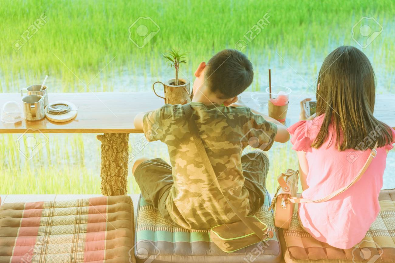 Back view of brother and sister are playing mobile phone games