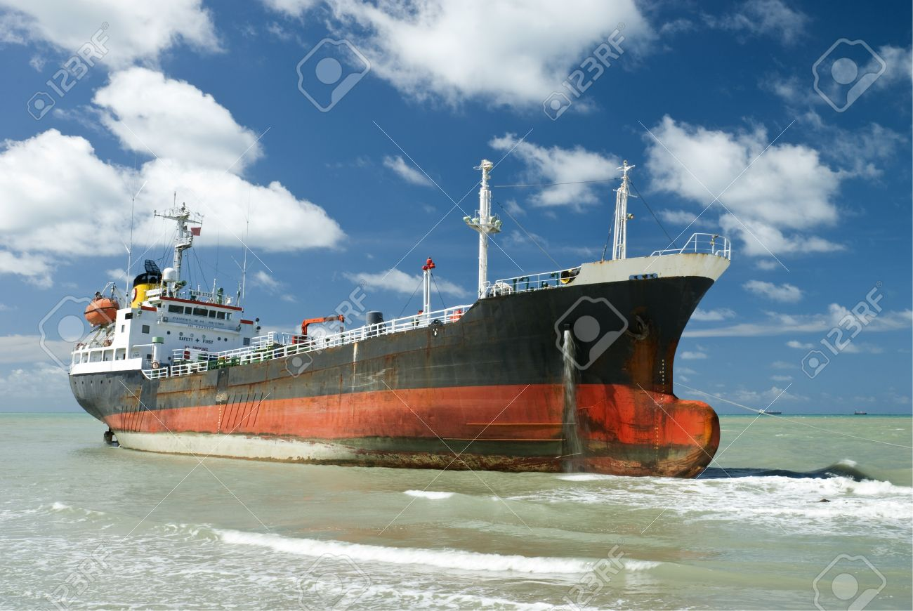 Cargo ship run aground on rocky  shore waiting for rescue Stock Photo - 13775796
