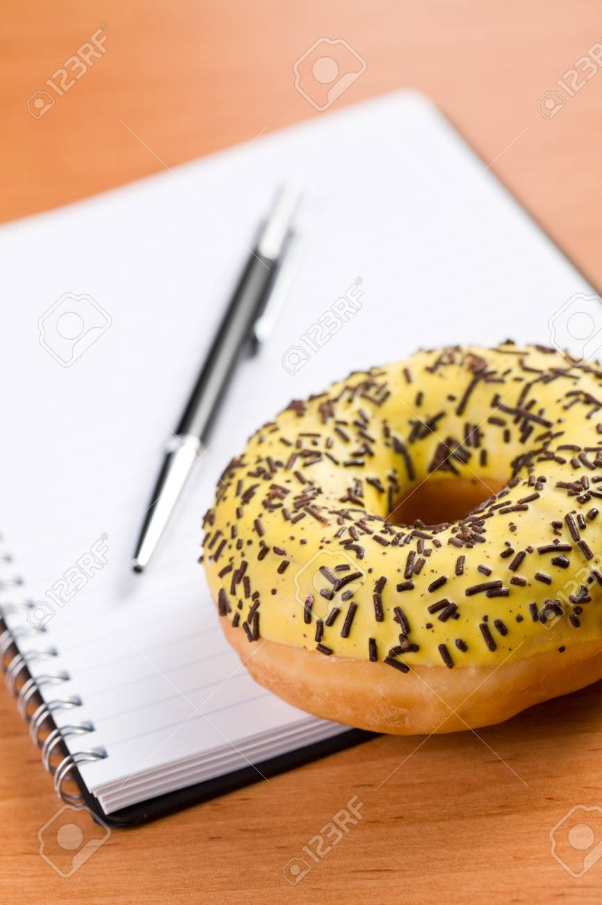 sweet doughnut and spiral notebook on wooden table Stock Photo - 8593167