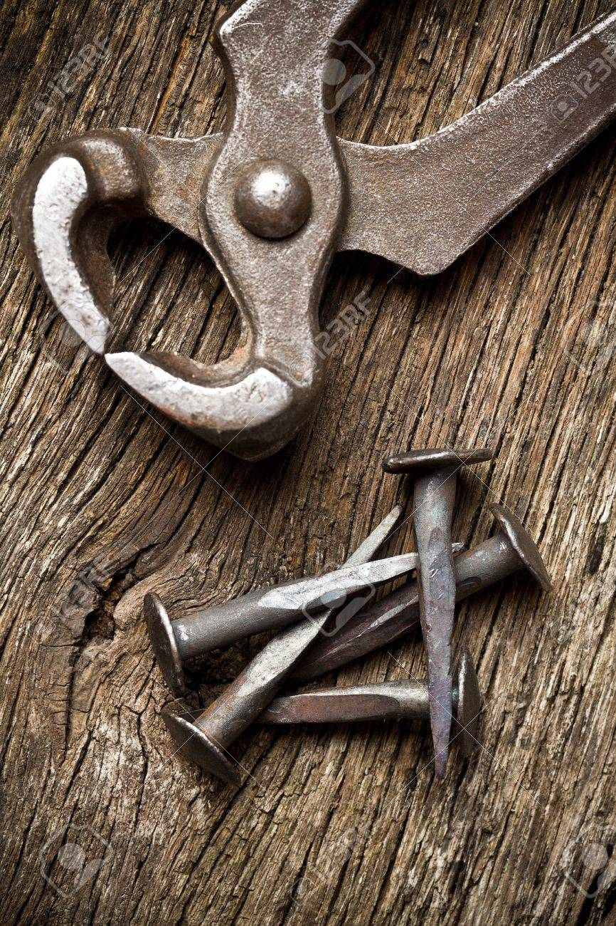 handmade nails with pliers on old background Stock Photo - 14385106