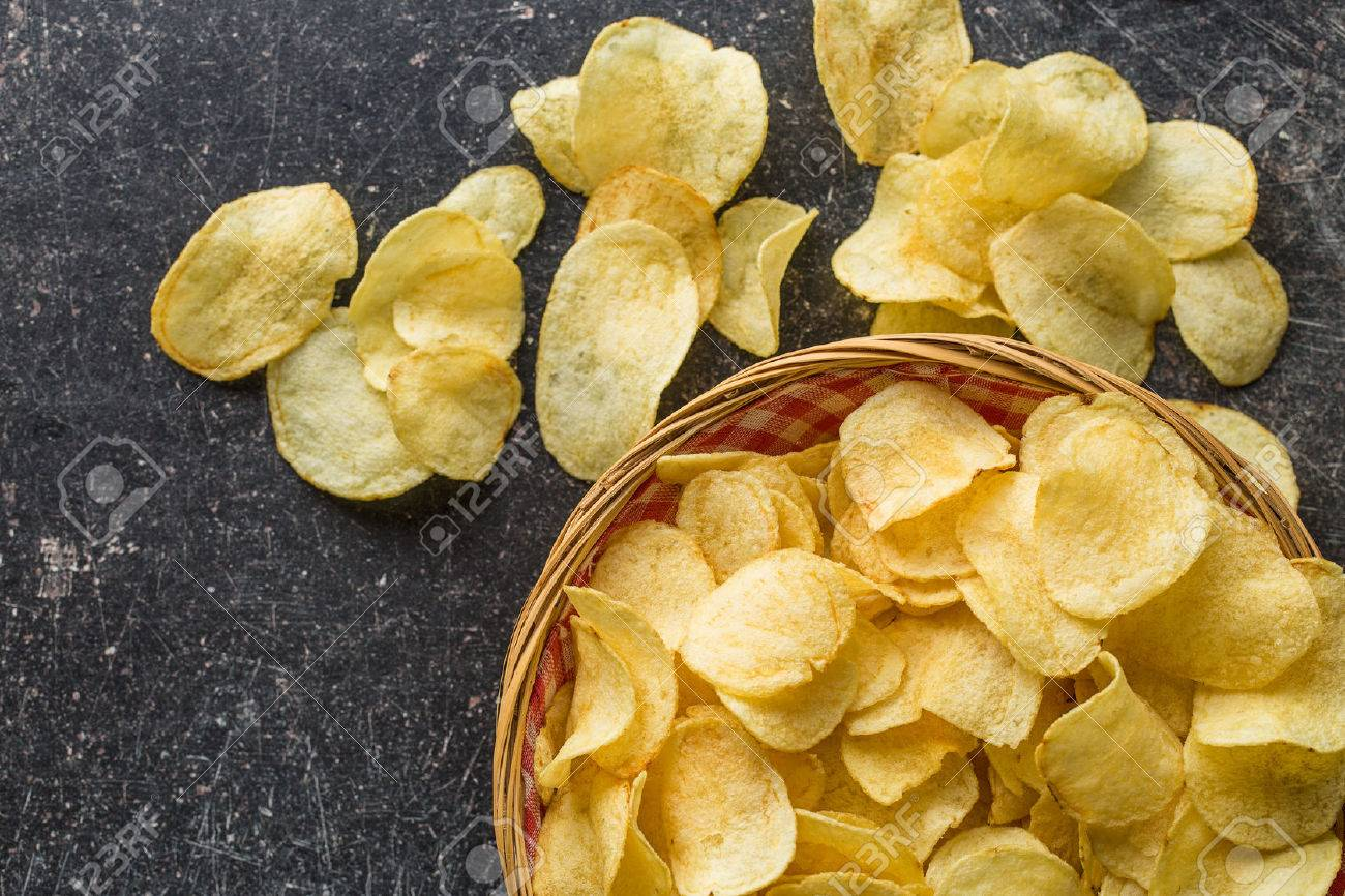 Crispy potato chips in a wicker bowl on old kitchen table - 55312346