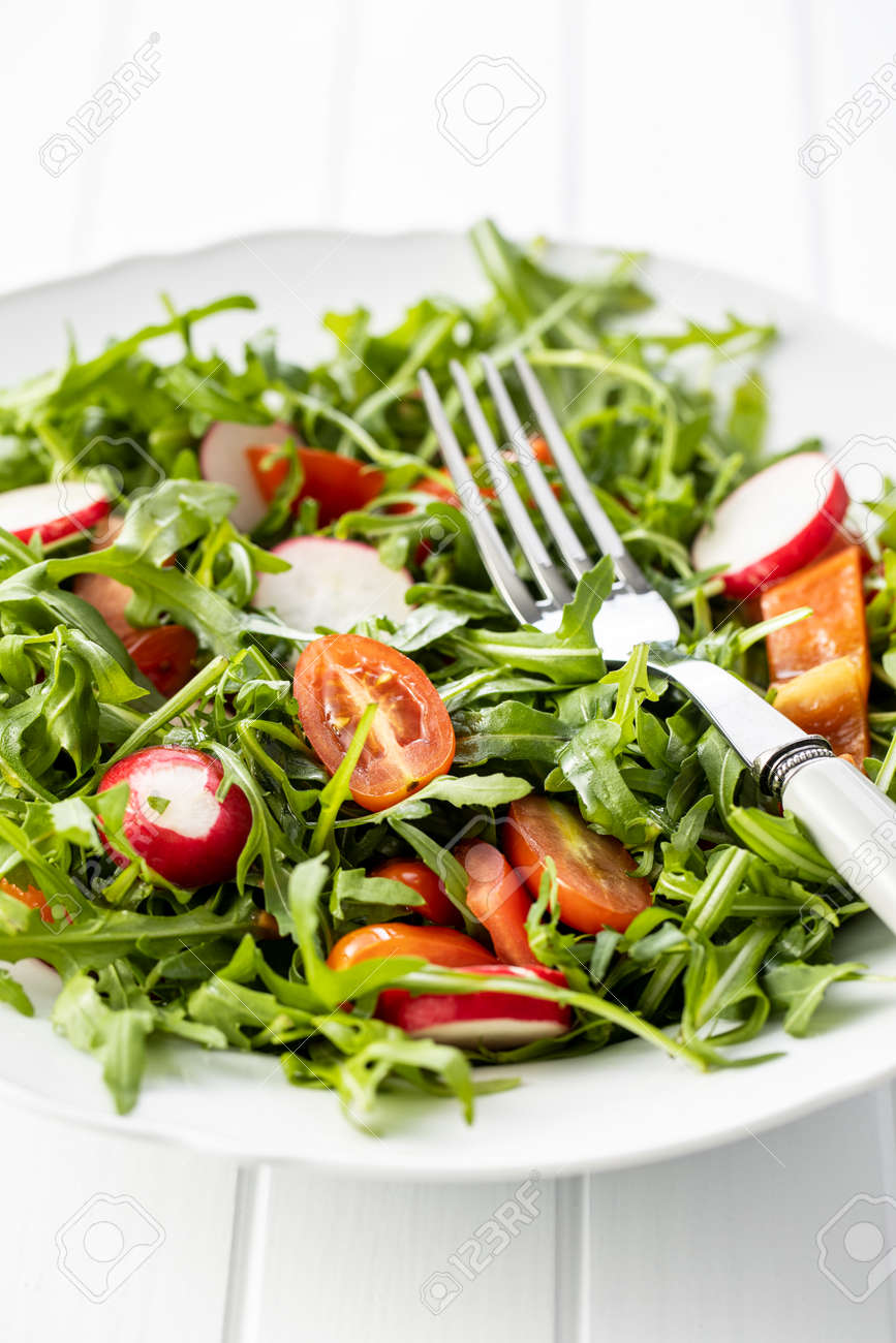 Fresh arugula salad with radishes, tomatoes and red peppers on plate. - 146022843
