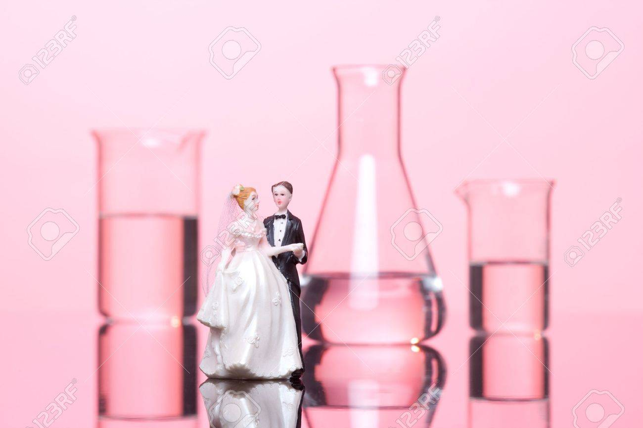 Chemistry of love concept. Wedding cake figurines and laboratory glassware against pink background. Stock Photo - 13026166