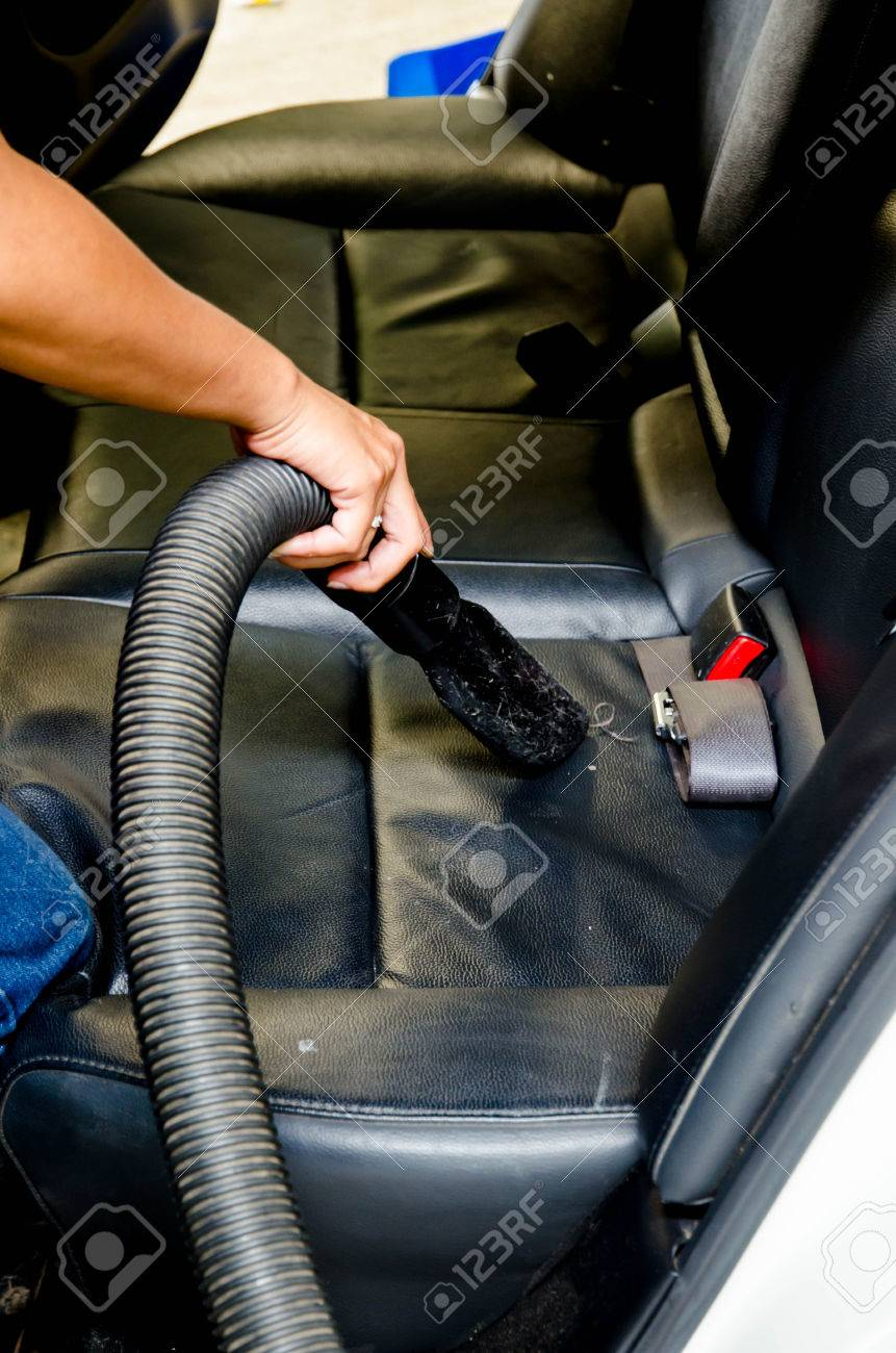 Hand vacuum cleaning dirt on a car carpet in car wash shop stock photo