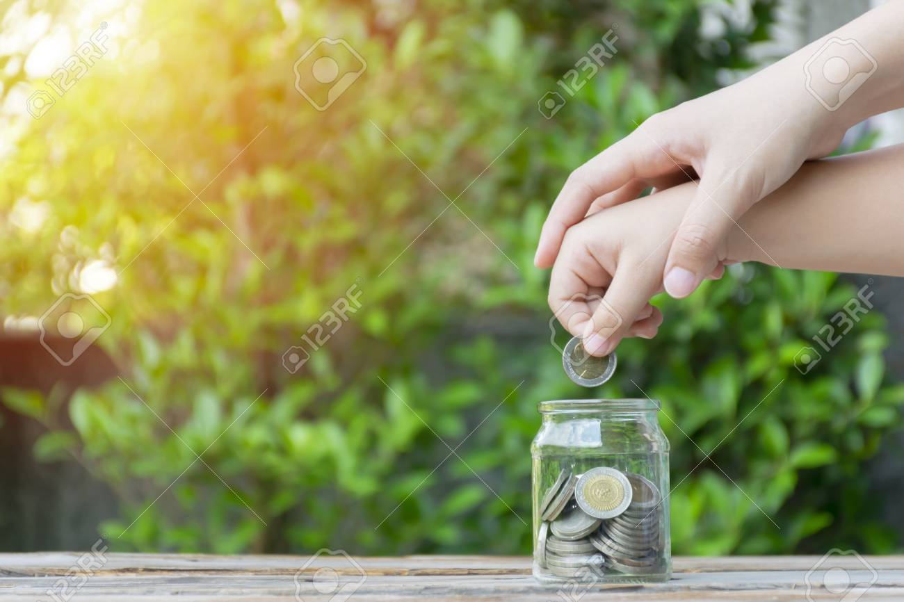 Little girl and pile coin for saving. money saving concept. girl and mother putting coins into glass bottle. To have a good future both in education and finance. This is the start of the investment. - 115915206