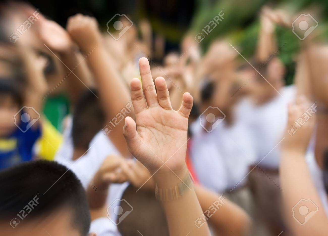 sharp hand raised in blury schoolyard background zooming in Stock Photo - 4189883