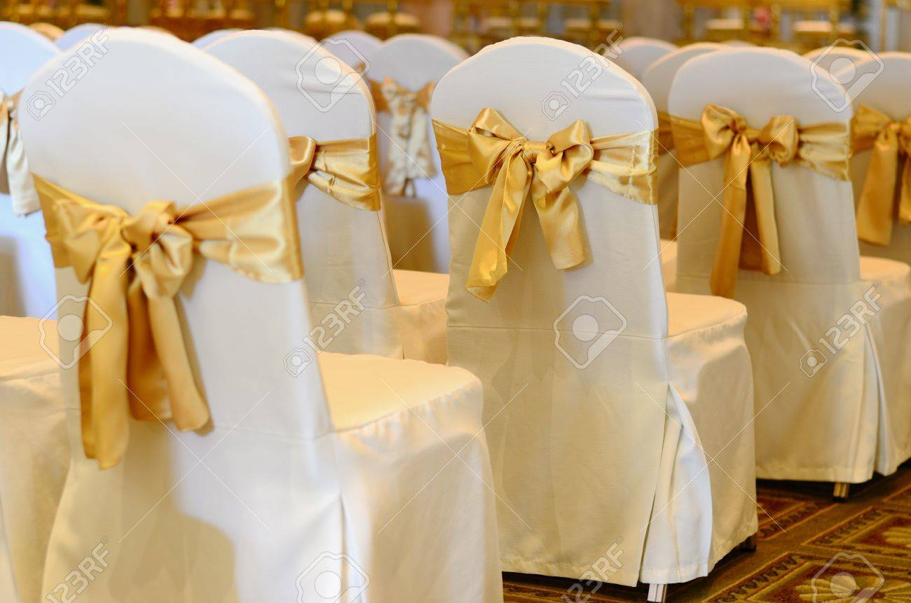 Stock Photo   Wedding Chairs In Row Decorated With Golden Color Ribbon.