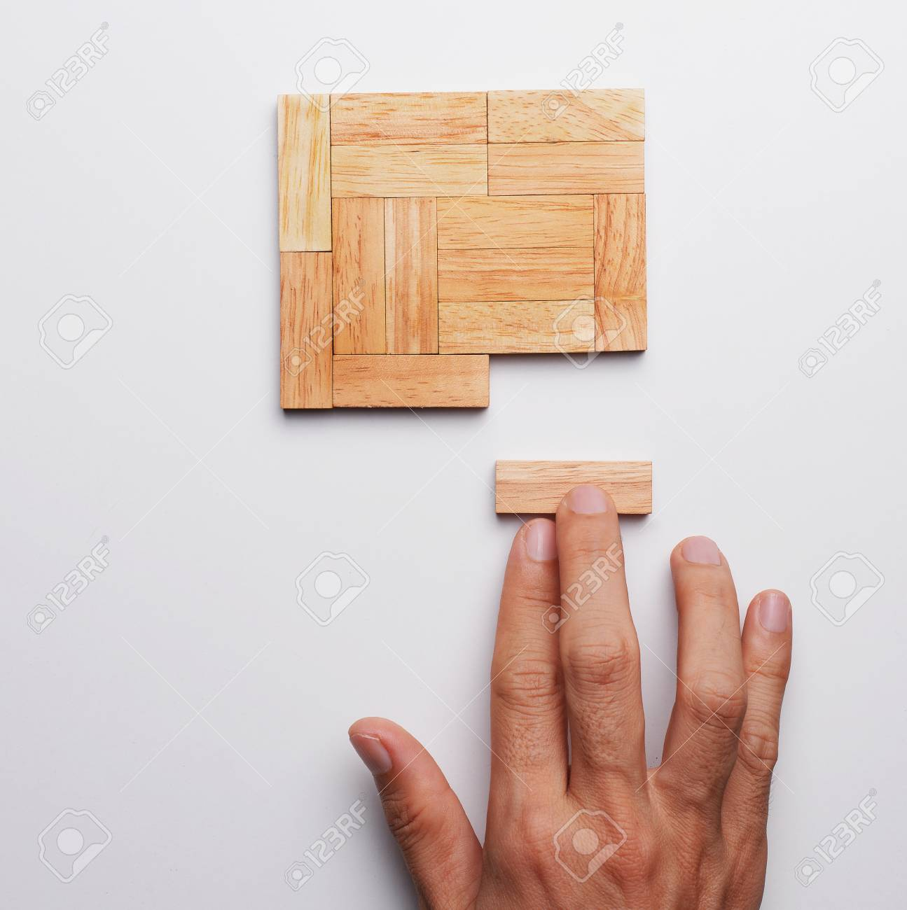 Man hand push last piece of wood block to complete the unity,