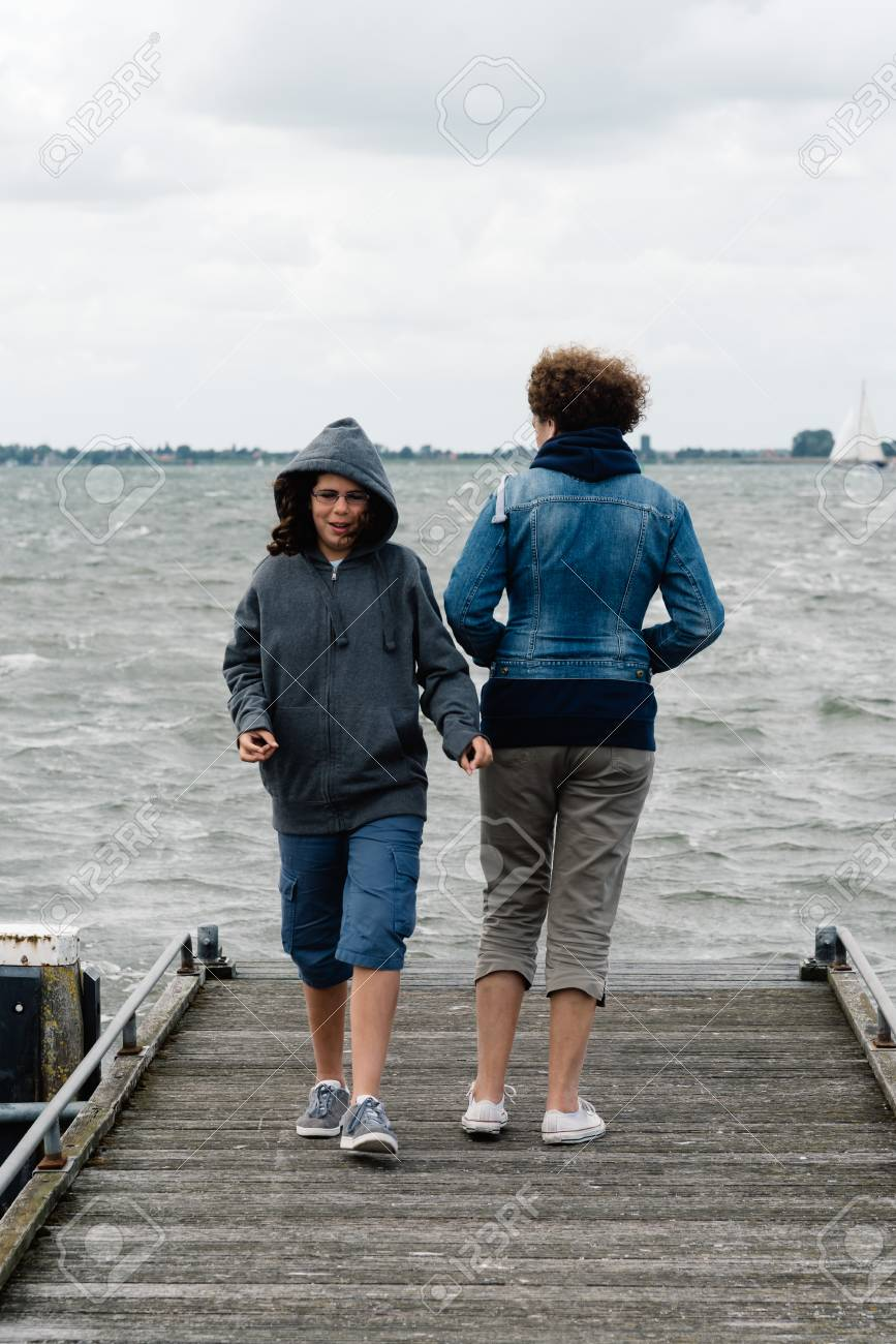 6e784ac35546 Stock Photo - Woman and girl on wooden pier a cloudy summer day. The woman  is standing back and the girl is walking to the camera. Concept family