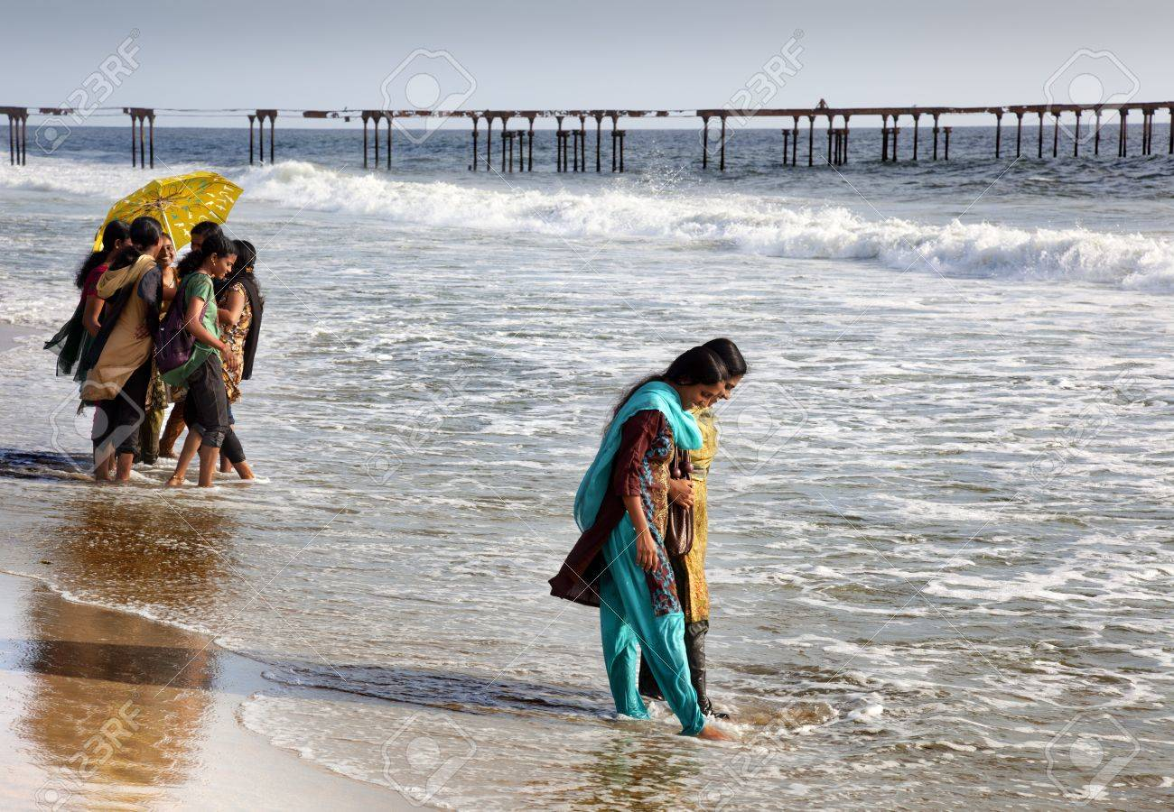 Allepey, India-September 6, 2012. Many Indian tourists come to the beach for a walk or swim. One of them appears as a wave wets her feet Stock Photo - 16376363