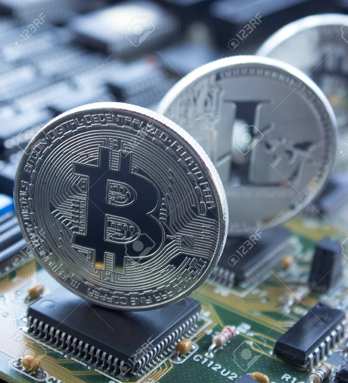 On a printed circuit board are silver coins of a digital crypto