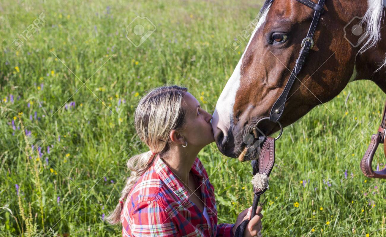 A young girl looks at horse and kissing her horse - 128510707