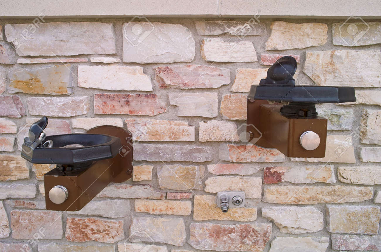 Two Drinking Fountains And A Hose Faucet On A Brick Wall Stock Photo ...