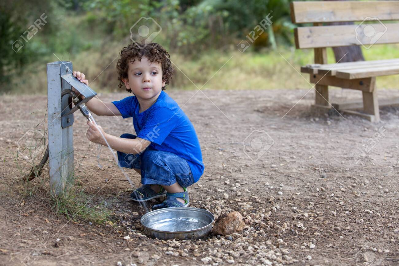 child opening a fountain for animals in park located in the middle of nature, - 154971564