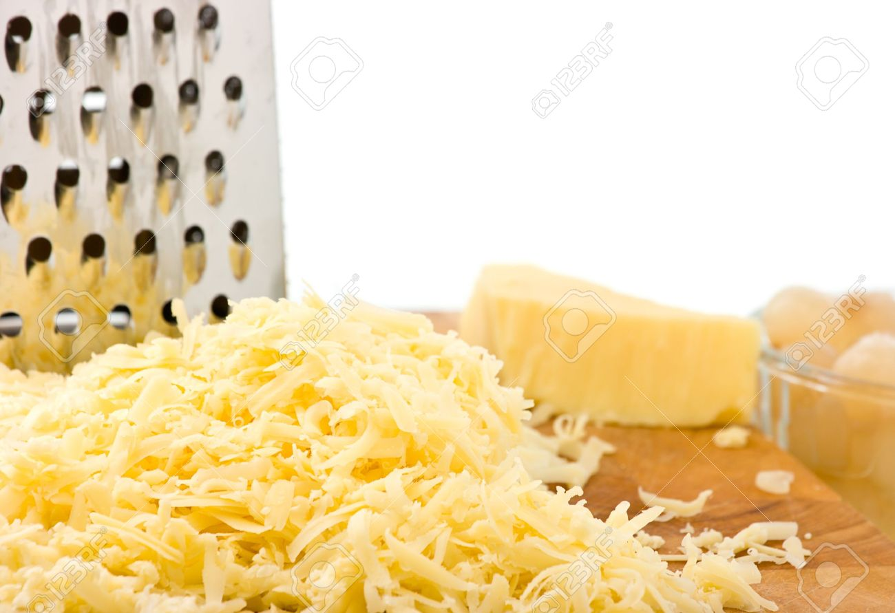Grated mild cheddar cheese on wooden board with grater and pickled onions focus on forground. White background for copy space. Stock Photo - 12204539