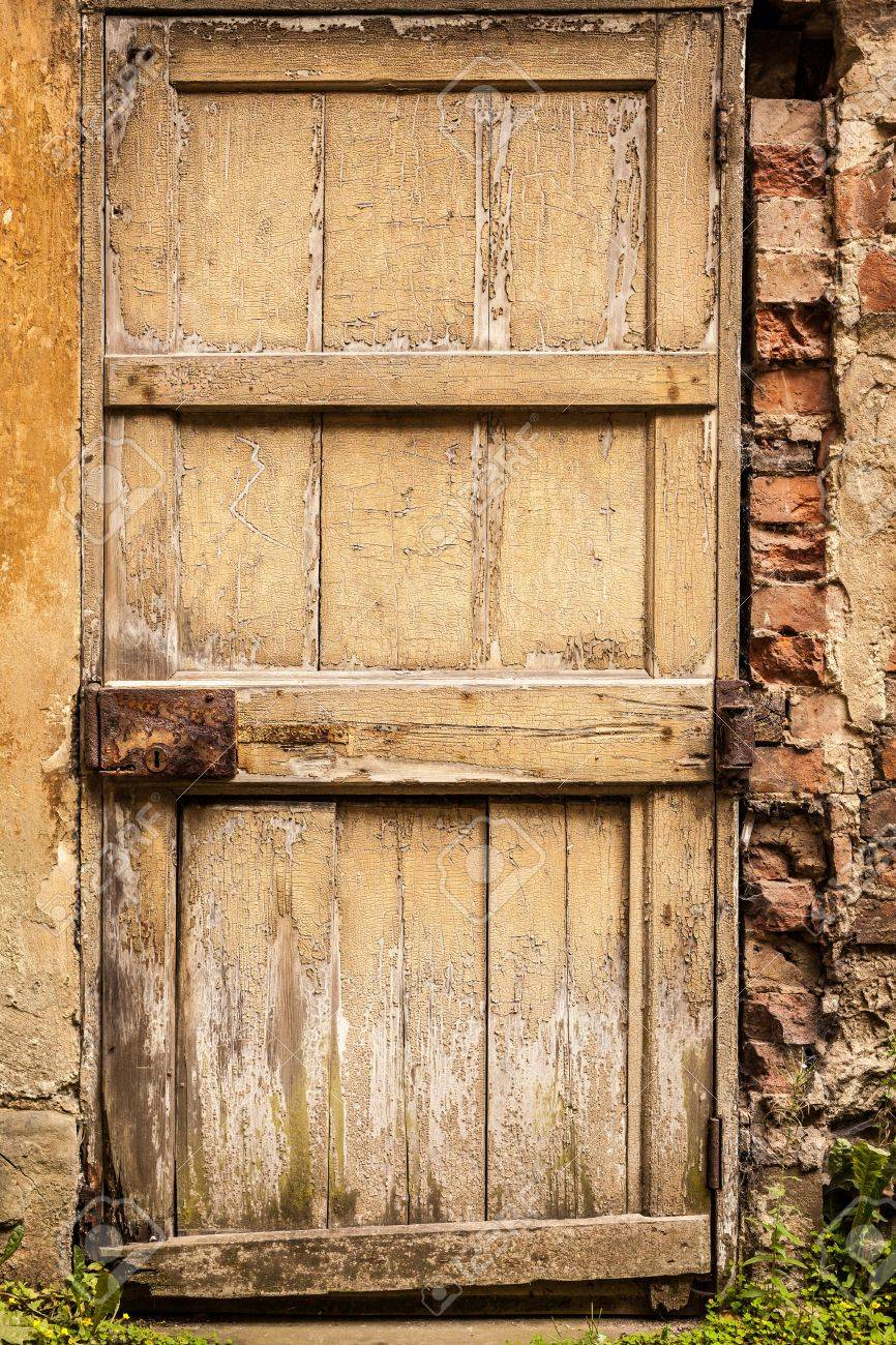 Old Wooden Exterior Door With Worn Cracked Yellow Paint And Rusty