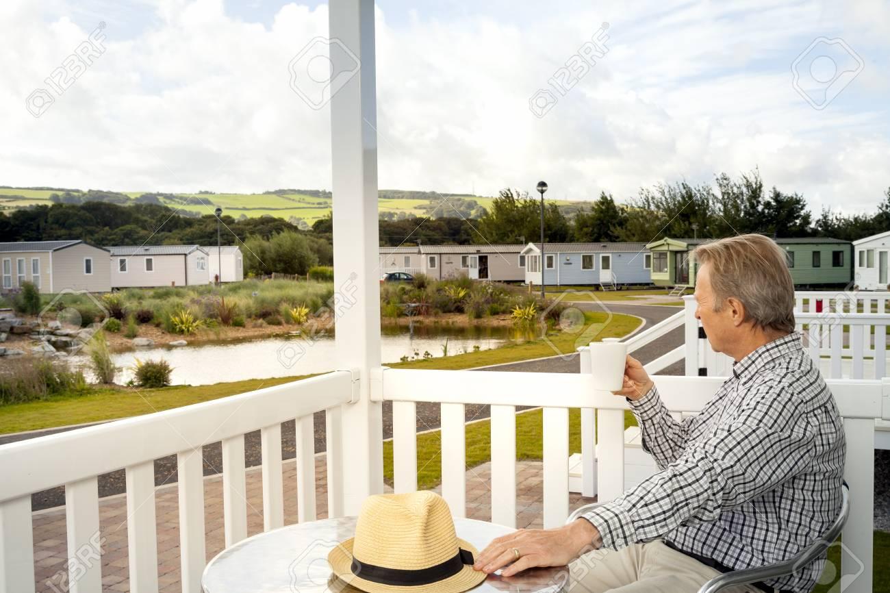 Anciano Bebiendo Una Taza De Café Sentado En La Terraza De Una Caravana Estática De Lujo En El Norte De Gales Teniendo En Las Vistas Panorámicas De