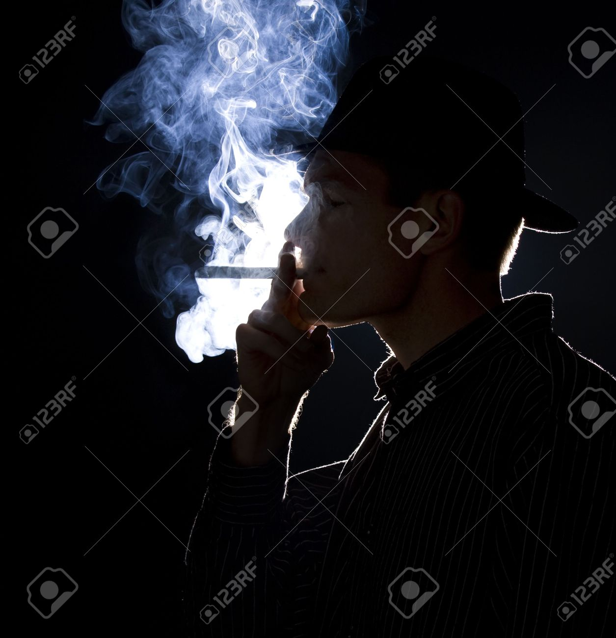 Backlit man smoking a cigar or cigarette with lots of smoke visible Stock Photo - 5371850