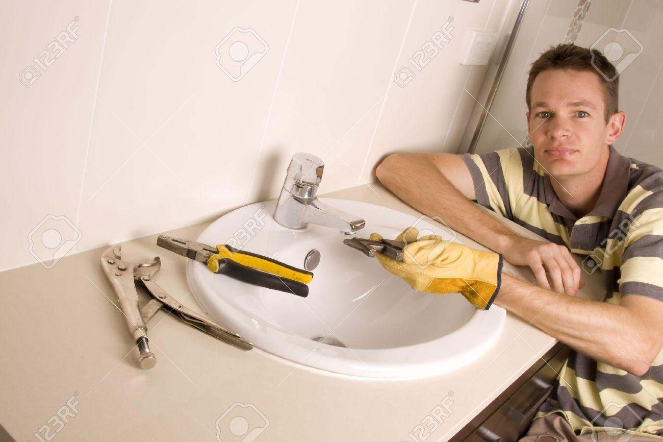 Plumber working on a broken tap in a bathroom sink - 5841139