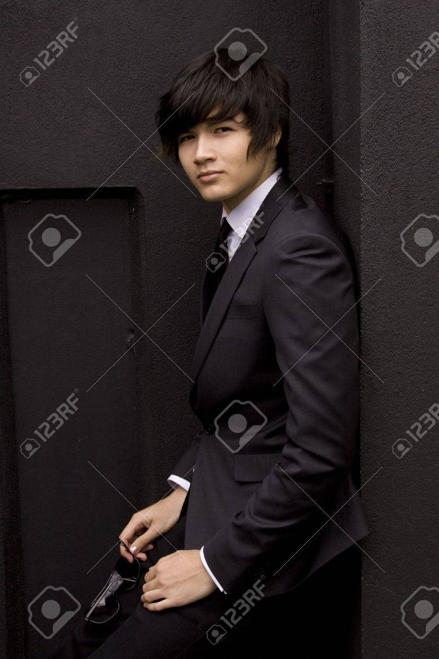 Young model in a black suit against a black wall - 6056470