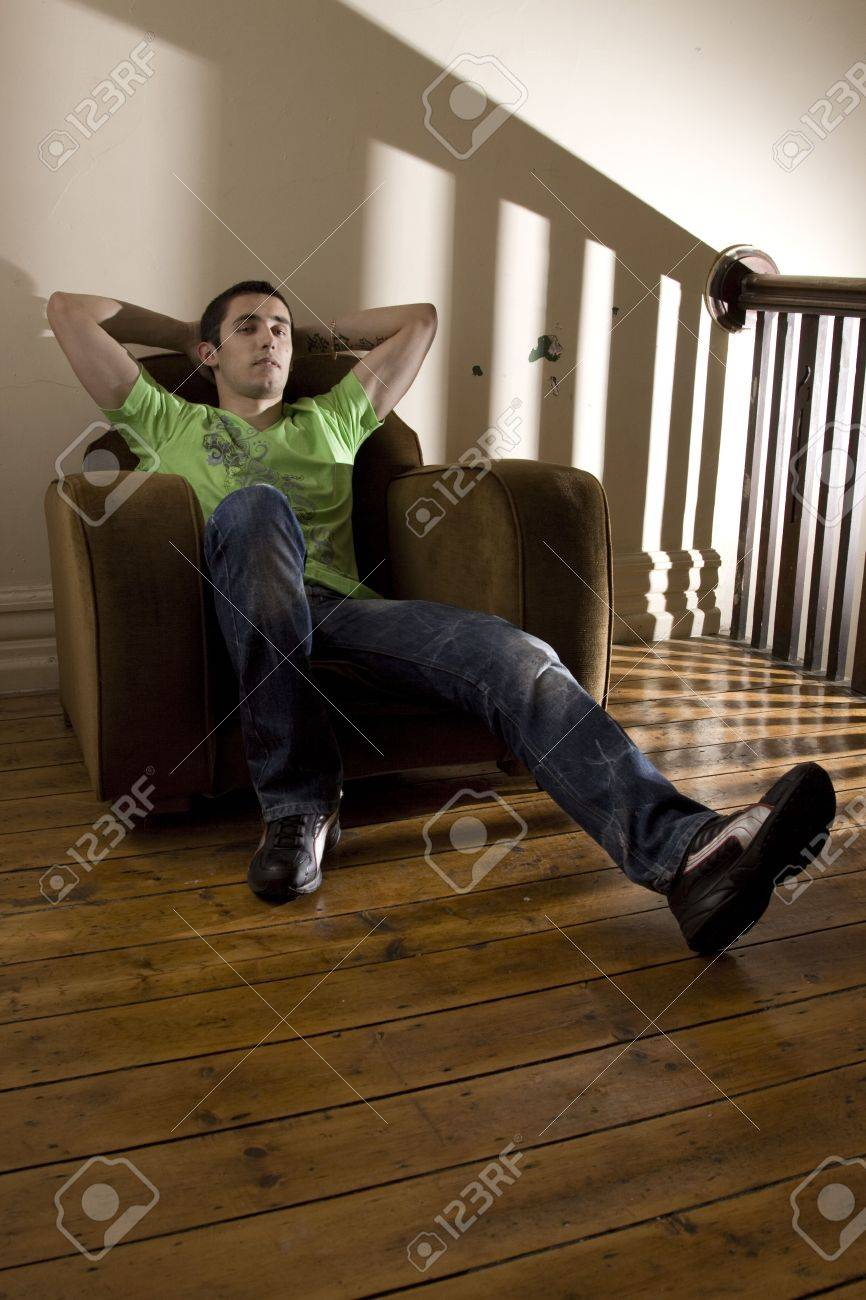 Young man lazing around in an old broken armchair Stock Photo - 6058727