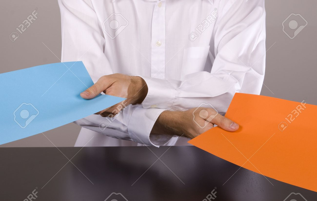 Man passing on two pieces of paper in opposite direction Stock Photo - 6302115