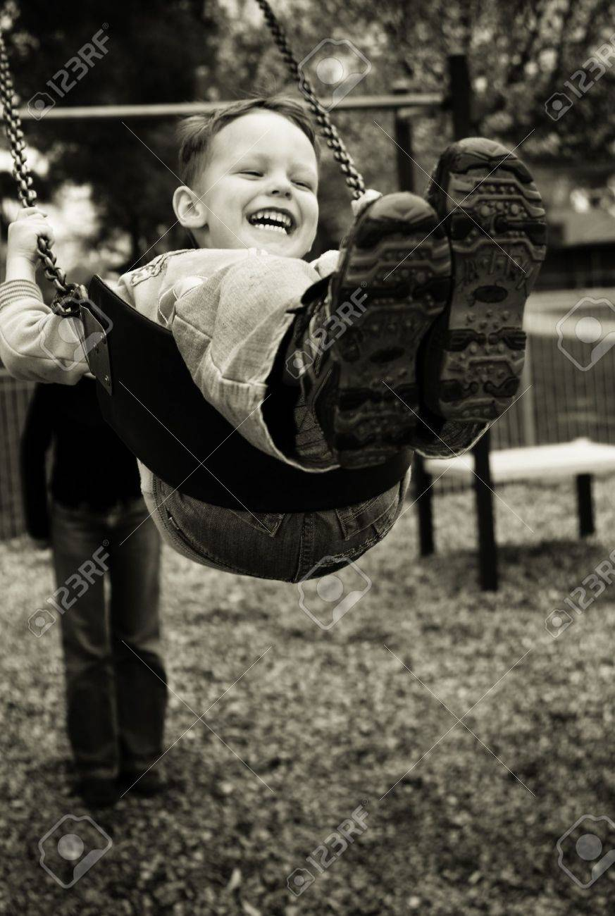 A little boy having a great time on a swing in a playground - 7873684