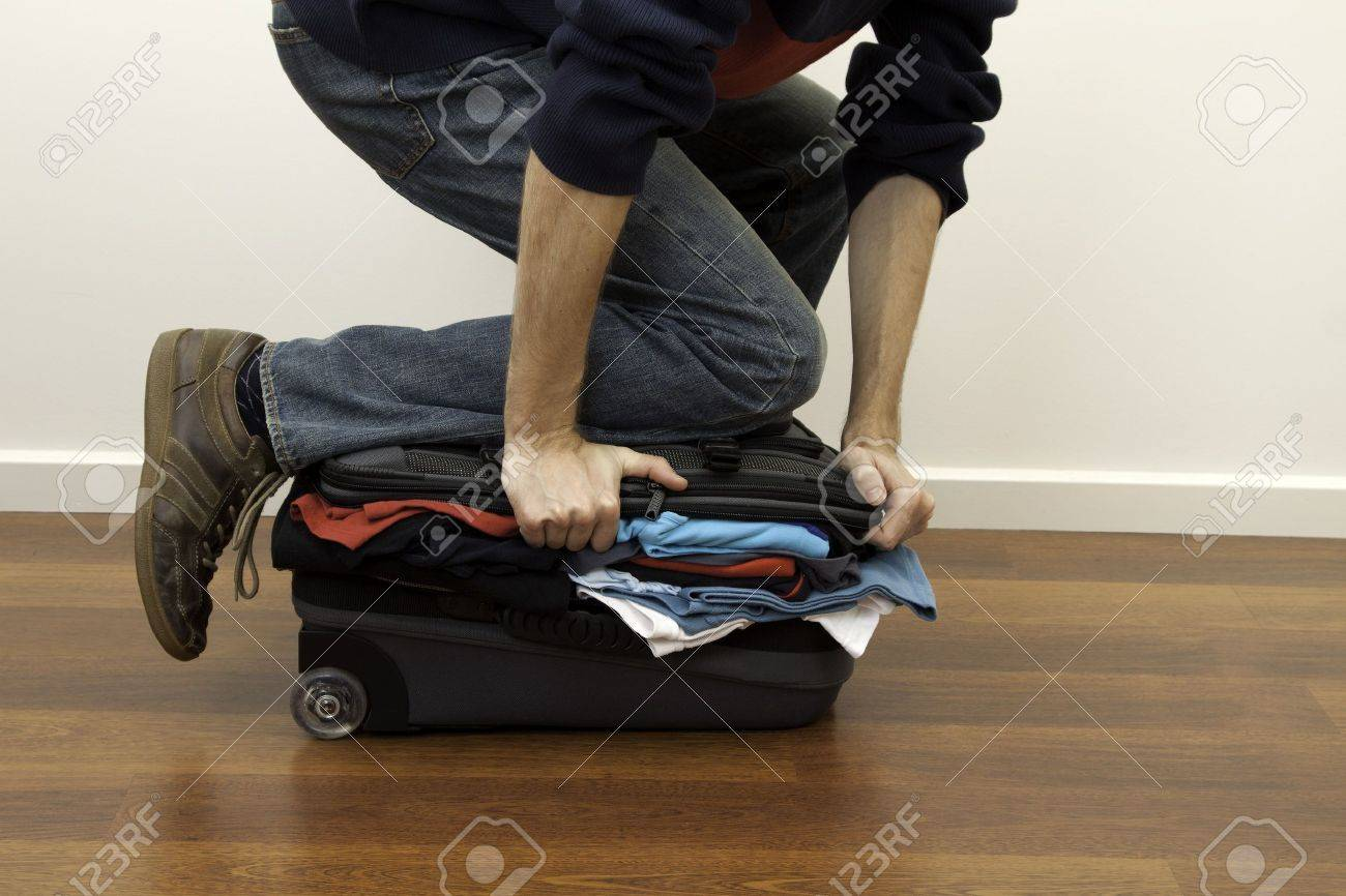 forcing the last few pieces of clothing into an over-full suitcase Stock Photo - 7917768