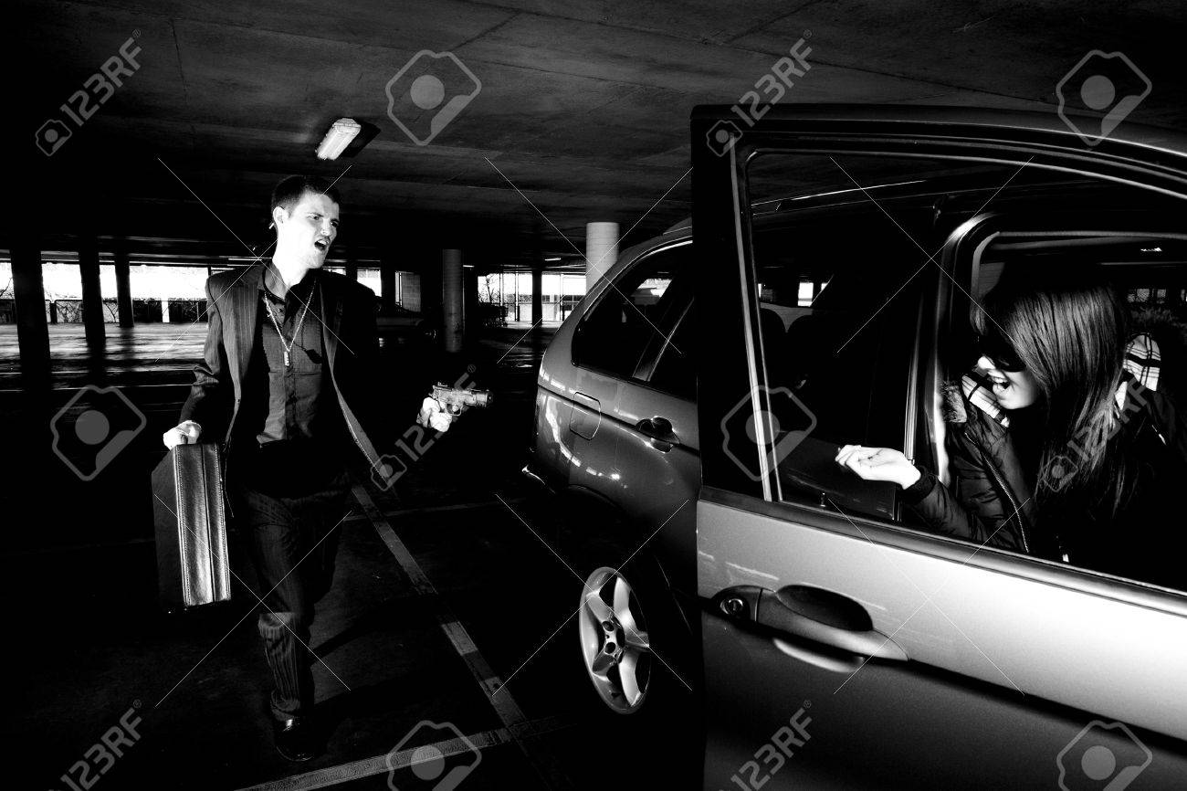 Guy with gun car-jacks a girl in a car - 8063137