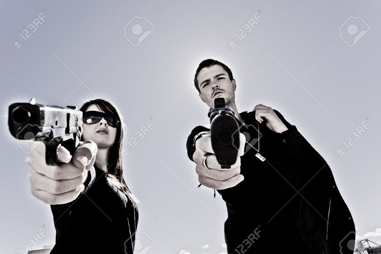Guy and a girl pointing two guns Stock Photo - 8063136
