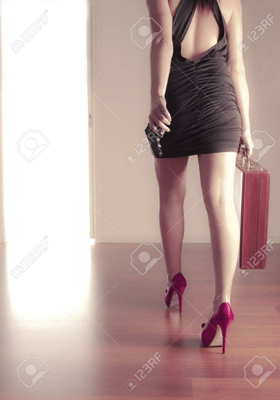 Girl with gun and briefcase walking out the door Stock Photo - 8144289