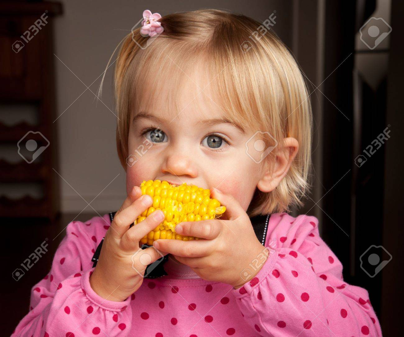 Closeup of a little girl taking a bite out of a corn on the cob - 10385555