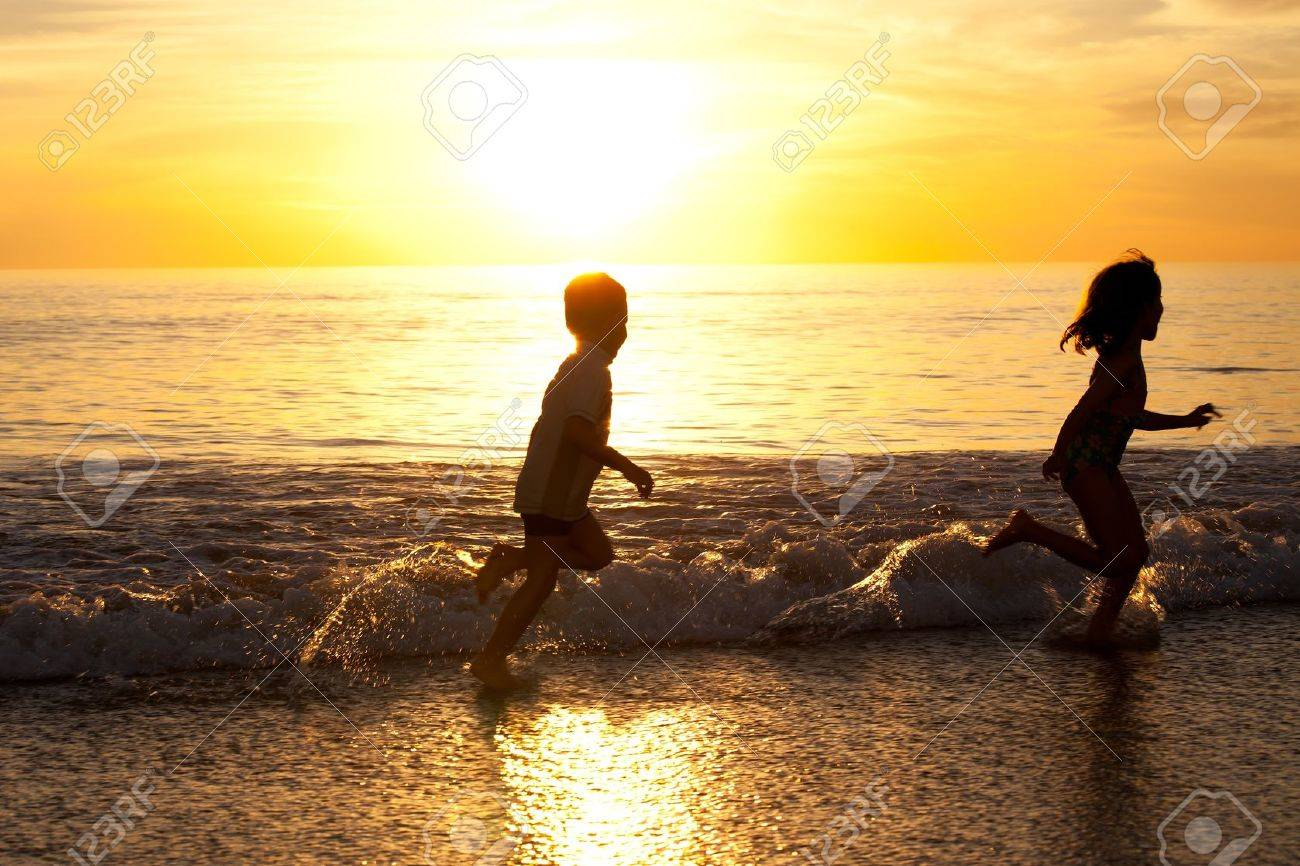 Two Kids Running In The White Wash Of Beach Stock Photo