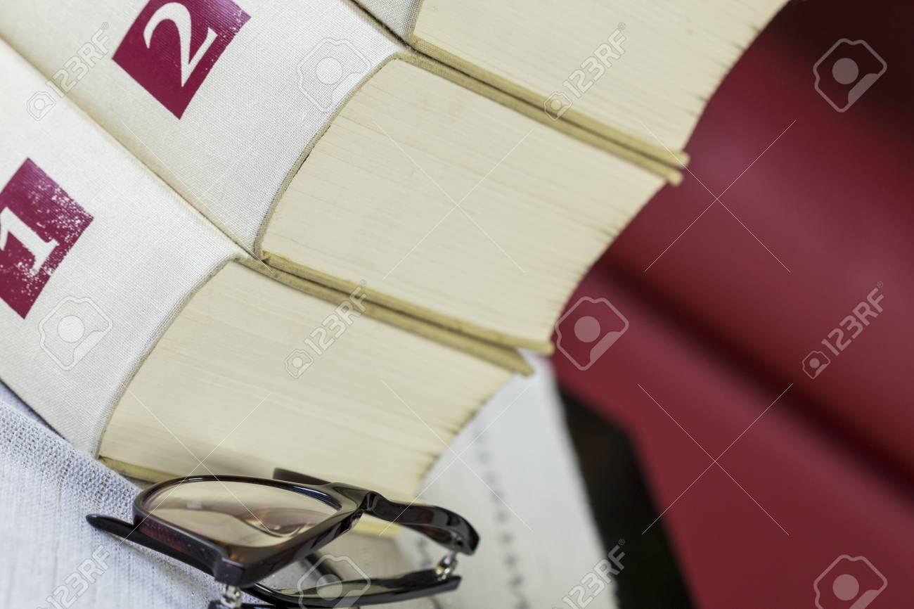 0adaeeaed7 Banque d'images - Paire de lunettes de lecture noires encadrées sur un  livre ouvert allongé sur une table avec nappe devant une pile de volumes  relié en ...