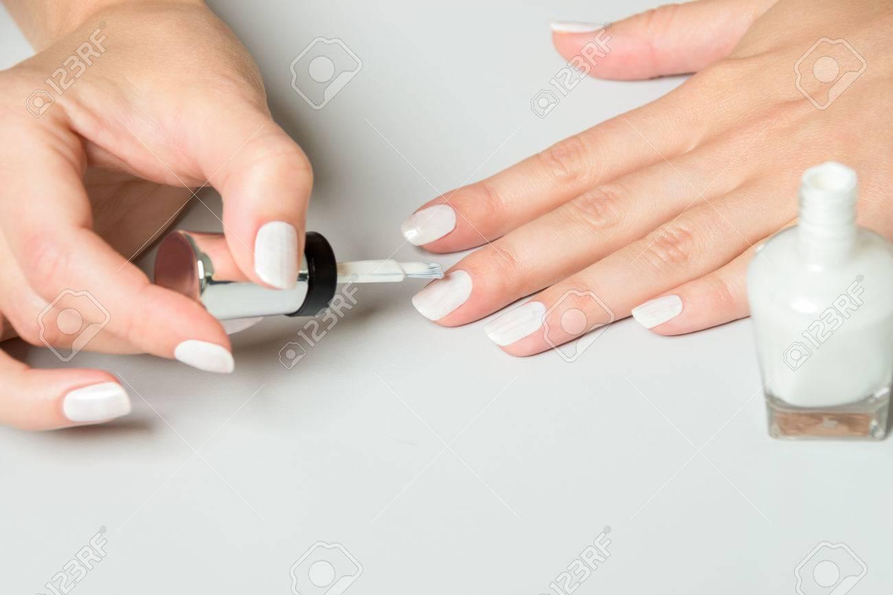 Close Up Of Woman Using Applicator Brush To Apply White Polish ...