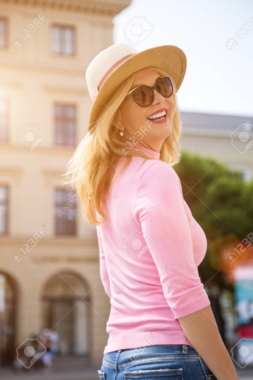 side view outdoor city portrait of smiling mature blonde woman