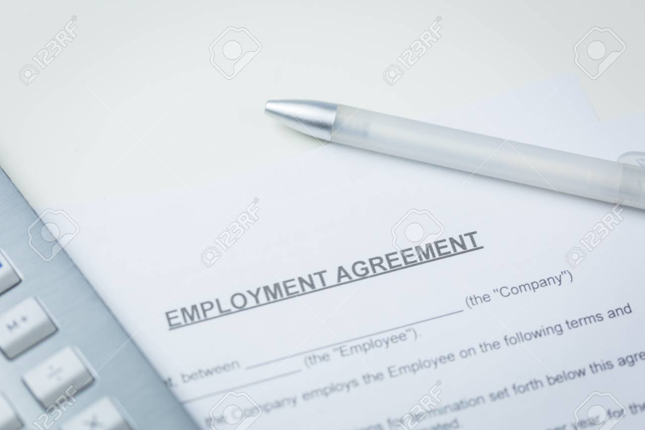 Agreement Of Employment With Pen And Laptop Lying On A Desk In