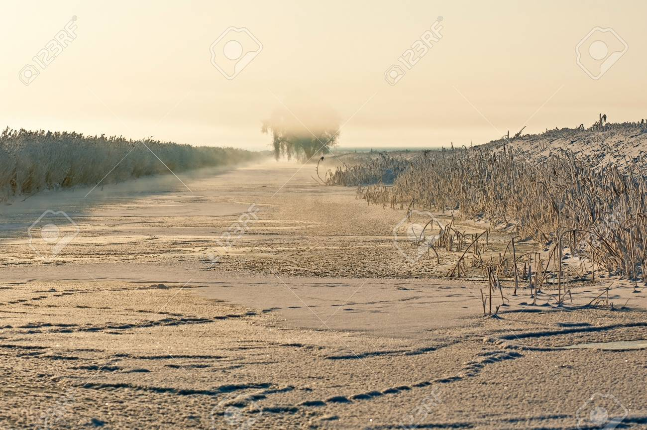 Sunrise over a frozen canal in winter Stock Photo - 12423554