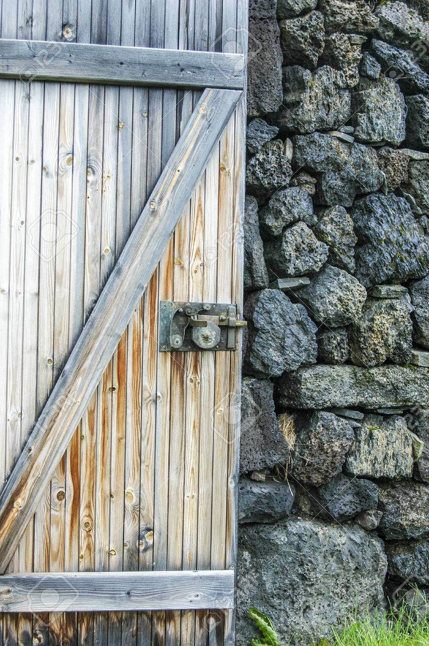 A Detail Of An Open Rustic Barn Door Against A Stone Wall With