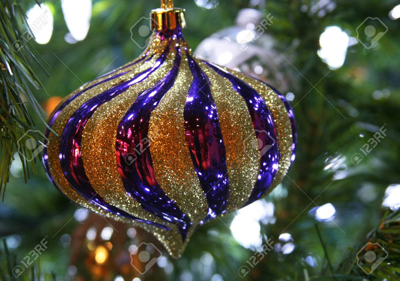 purple and gold christmas ornament hanging on tree stock photo 24629398