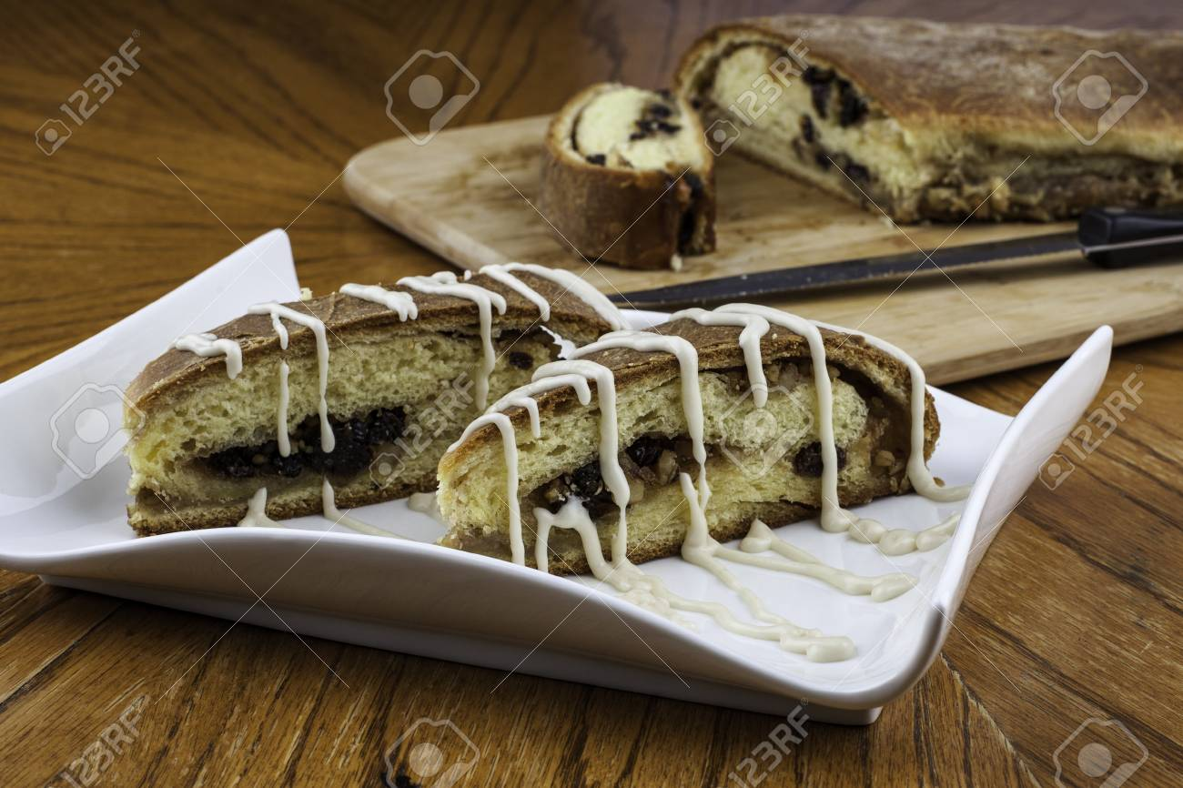 Nicely plated iced raisin nut bread with loaf and knife in backgound on wood cutting board Stock Photo - 16882419