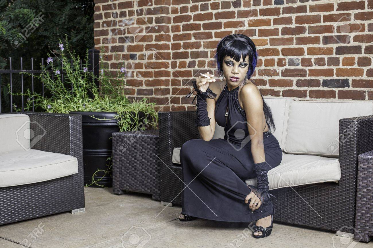 Sexy african american gothic woman smoking. Sitting on a couch outddor patio, space for text. Stock Photo - 17539244