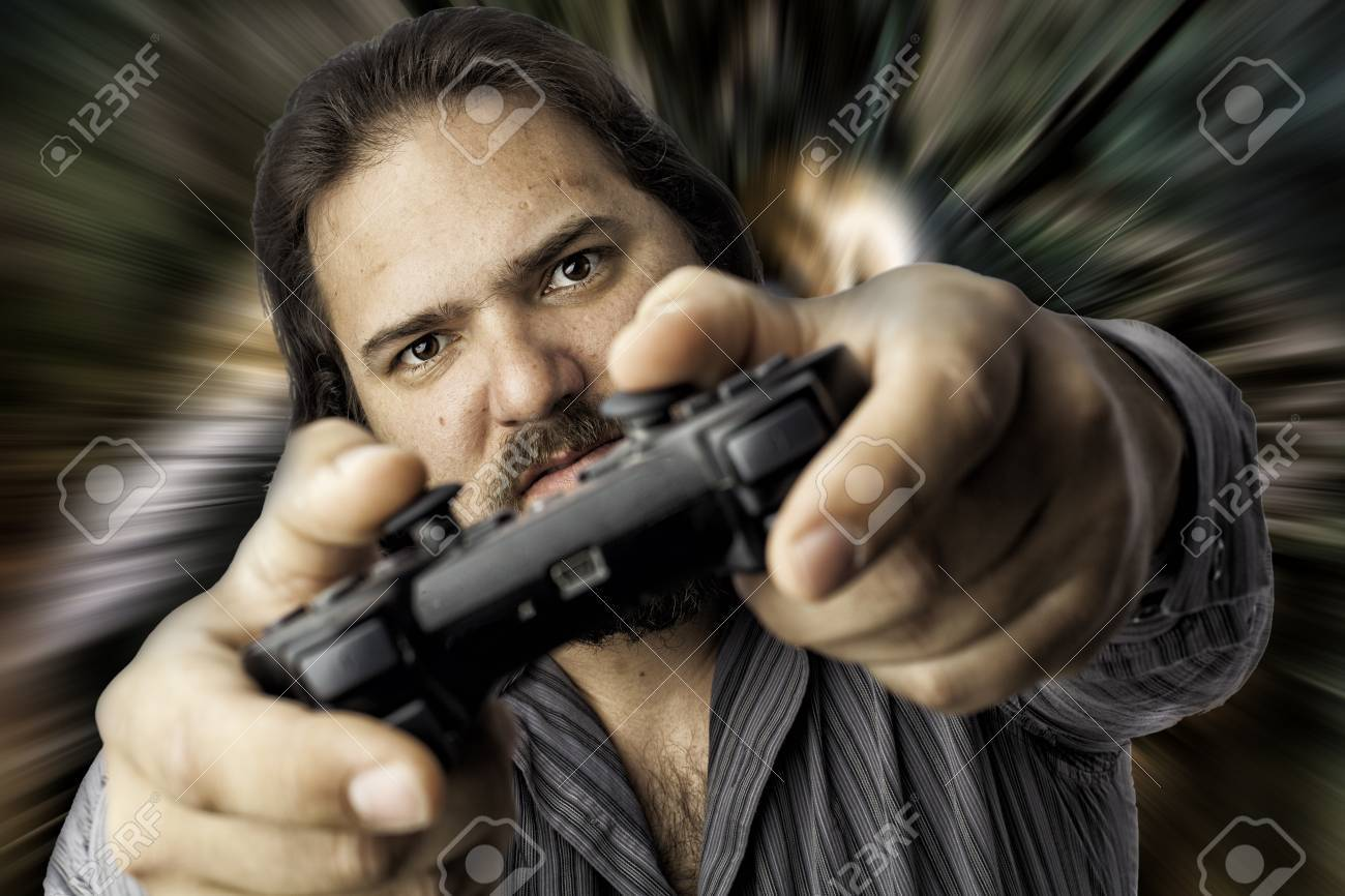 Young white male using a video game controller with a smile. Isolated portrait on white with copyspace, eyes in focus with blurred controller in front, Stressful look on his face Stock Photo - 17539261