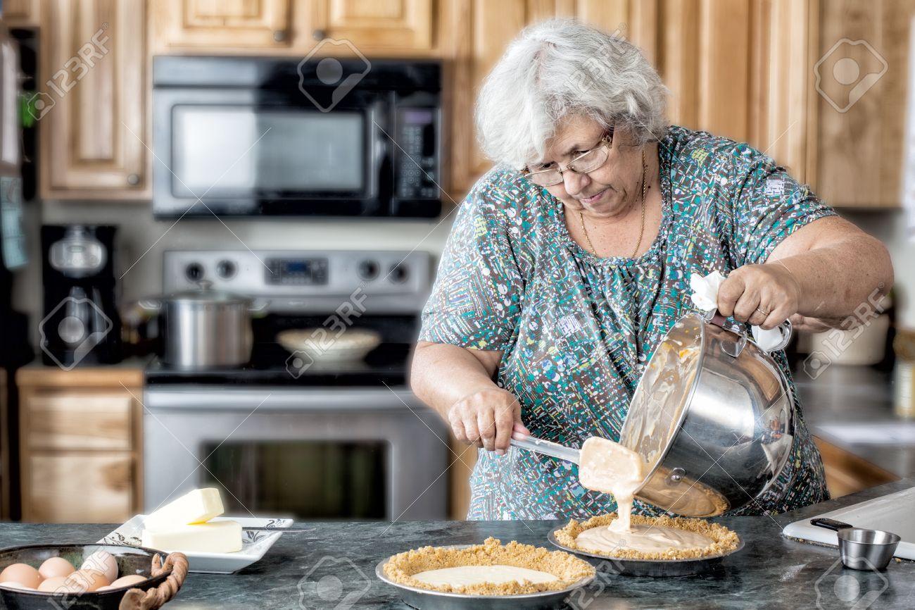 archivio fotografico foto di una donna anziana nonna attiva in una cucina naturale di riempimento torte bianco donna anziana nella cottura cucina