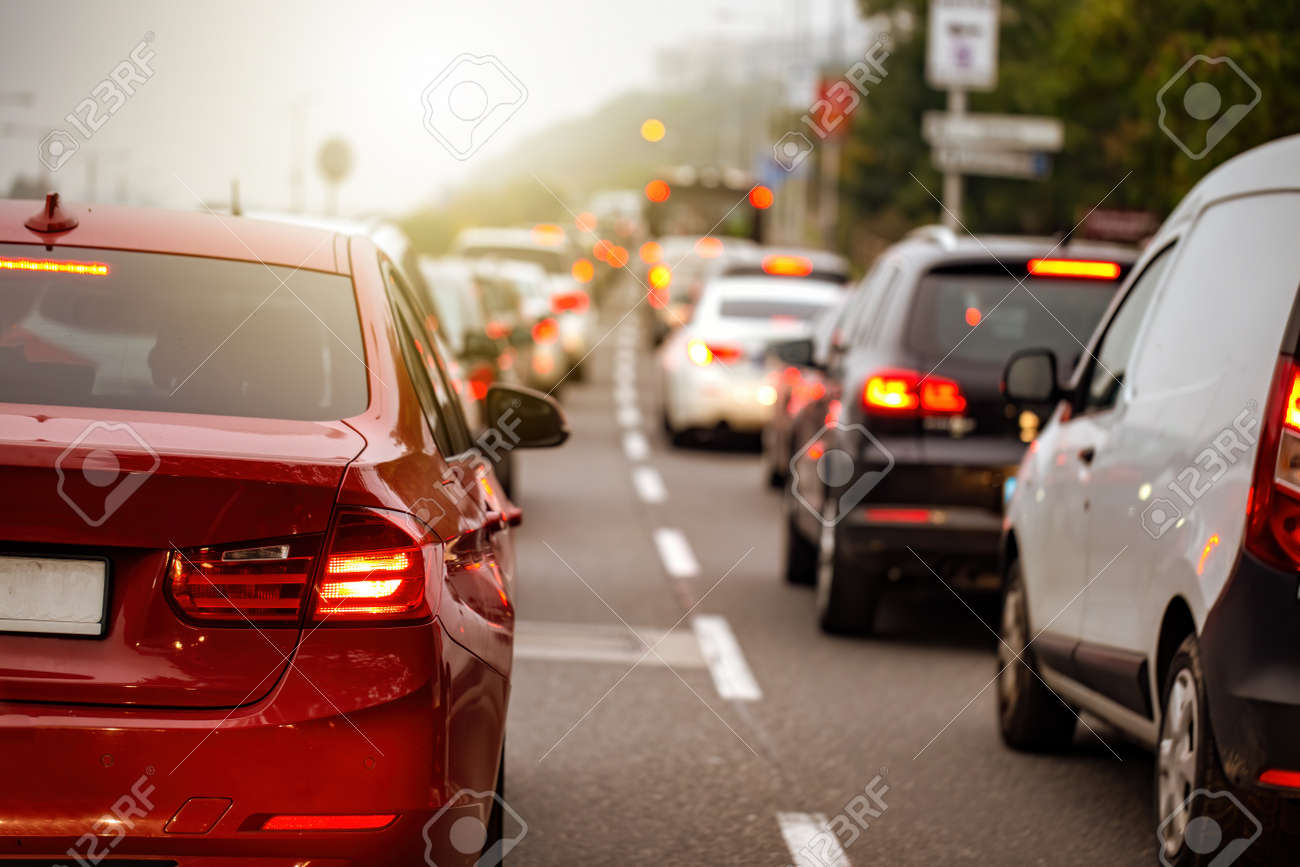 Traffic jam in a city with long queue of cars waiting on a road at sunset. Concept of stress from being late during commute. Street crowded with stopped vehicles. - 158424485