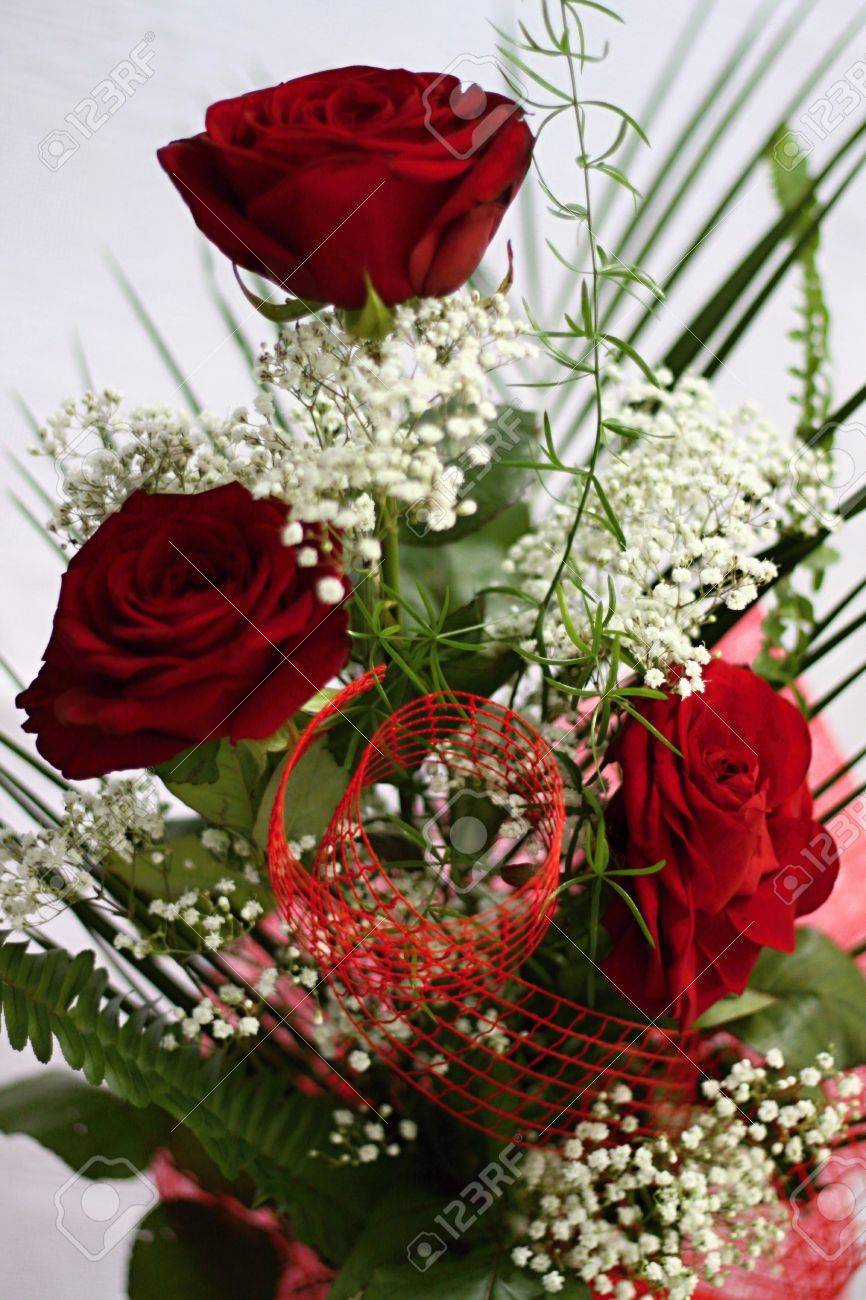 Three red roses and whitte flowers with green leafs Stock Photo - 16908805