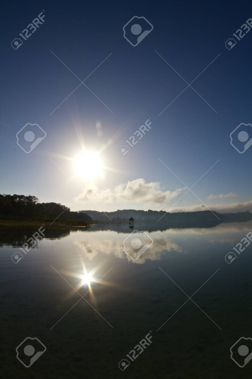 Lake Peten becomes a mirror to reflect the morning sun. Stock Photo - 9055851