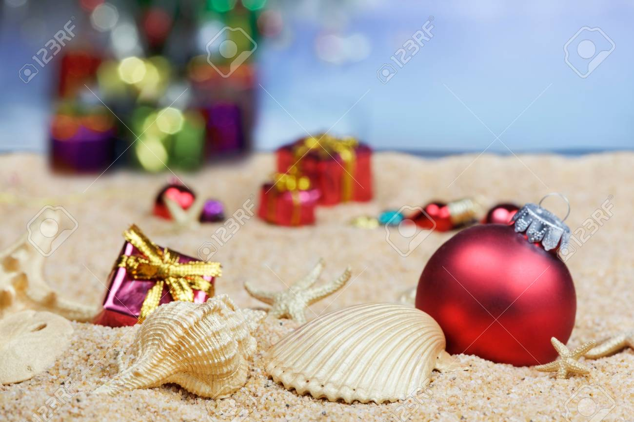Christmas beach ornaments - Christmas Ornaments And Shells In The Sand Stock Photo 9821061