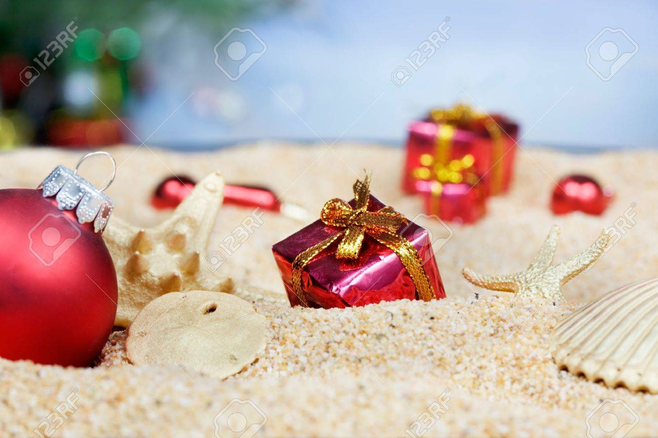 Christmas beach ornaments - Christmas Ornaments In The Sand Red Packages Stock Photo 9821339