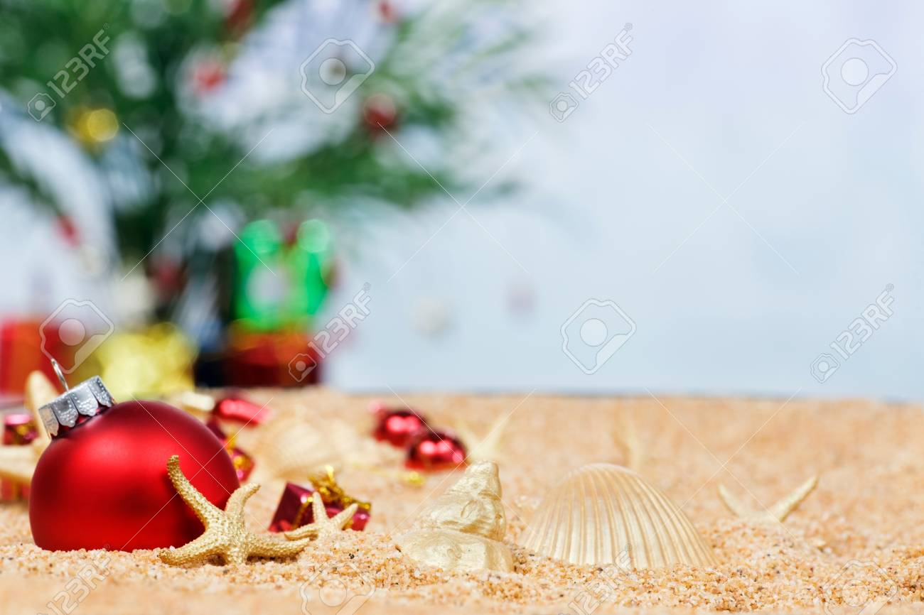 Christmas beach ornaments - Christmas Ornaments And Shells In The Sand Stock Photo 9821594